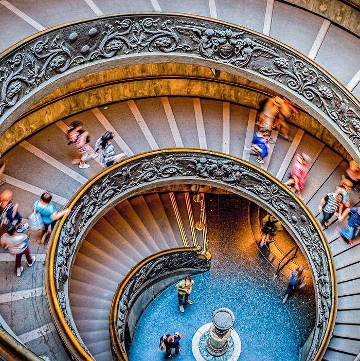 A large spiral-staircase decorated with stucco, photographed from above. People are walking up and down the stairs.