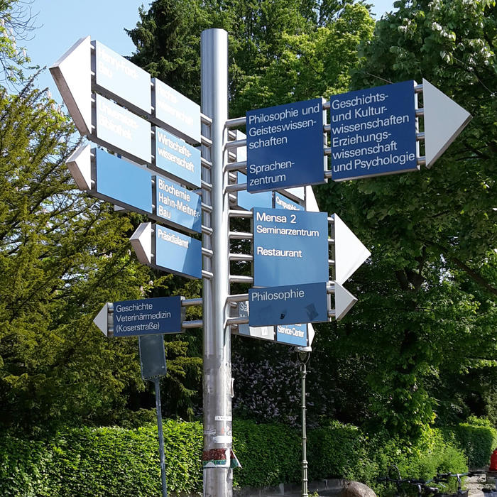 A signpost indicating the way to various buildings of Freie Unviersität Berlin.