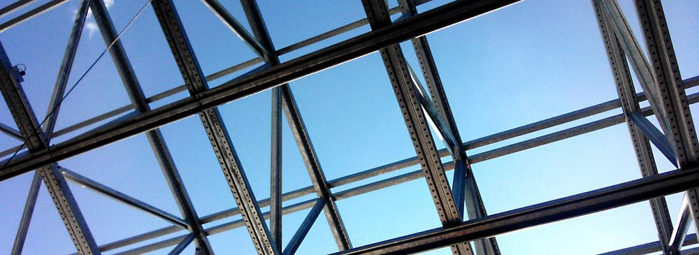 Metal and glass framework of a roof with blue sky in the background.