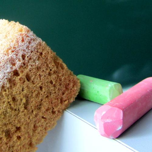 A sponge, a green stick of chalk and a pink stick of chalk in front of a blackboard.