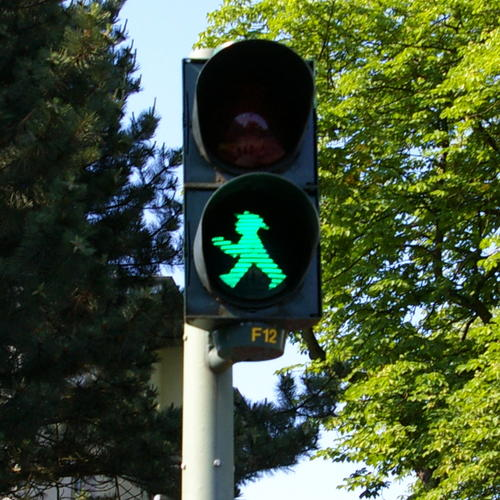 A green pedestrian signal. In the background there are trees with full green foliage.